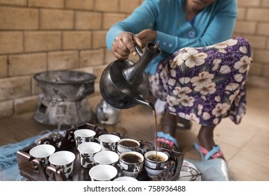 Closeup of Ethiopian womans hands as she pours coffee in Ethiopian coffee ceremony.