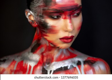 close-up Eurasian girls with dark hair and clear skin, and brown eyes, on a black background, in makeup red ottenkami on the face in the form of strokes, and delicate red lips
