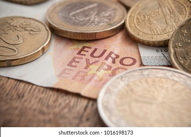 closeup of euro coins and bank notes on wooden table background