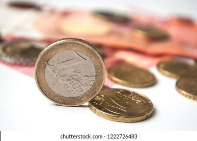 closeup of euro coins and bank notes on white background