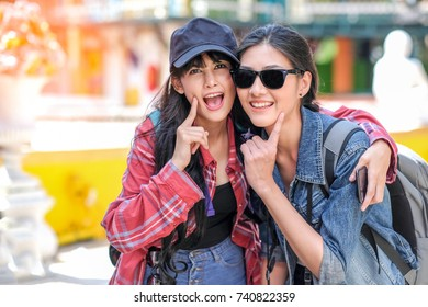 Close-up of excited cheerful smiling young beautiful girls in sunglasses taking selfie on summer city street. Urban life concept.Hipster girls wearing hat and sunglass enjoying selfie in colorful city