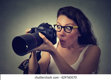 Closeup excited shocked woman with professional DSLR camera isolated on gray wall background