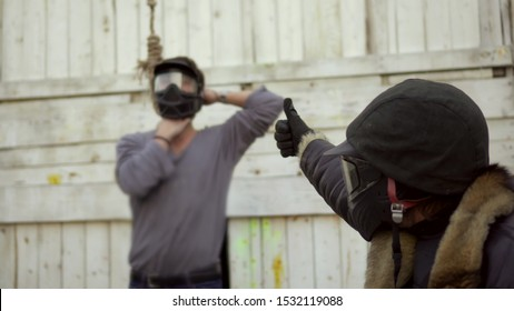 Closeup executioner in mask sentence man death, killing him on gallow noose around neck 4K. Manifestation cruelty torture victim on gallow through loop death. Hangman show thumb down condemning death.