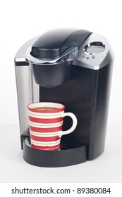 Closeup of expensive coffee maker with mug of fresh brewed coffee and beans around over white