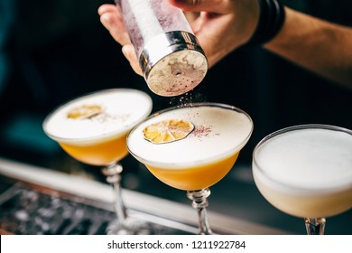 Close-up of expert bartender making cocktail on the bar, blurred background.