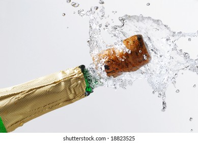 Close-up of explosion of champagne bottle cork studio isolated on white
