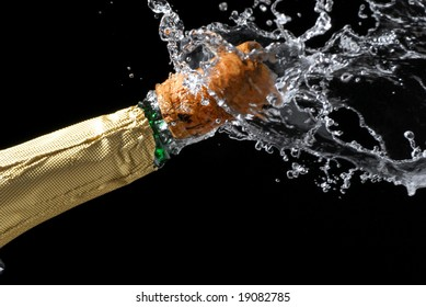 Close-up of explosion of champagne bottle cork with dark background