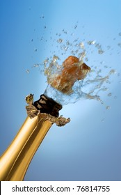 Close-up of explosion of champagne bottle cork with blue background