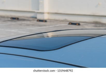 Closeup of exterior glass of sunroof in top of automobile parked in lot on sunny day.