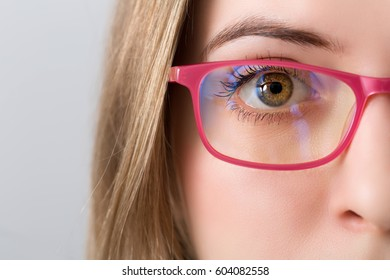 closeup of and eye and brown iris of blonde woman with pink glasses