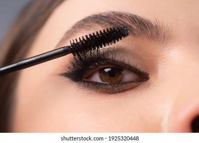 Closeup of eye makeup. Applying maskara on lushes Young woman getting make up with brush. Eyes visage woman