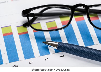 Close-up Of A Eyeglasses And Ballpen On Financial Graph