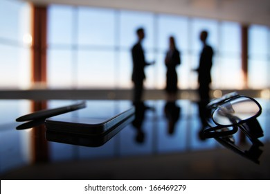 Close-up of eyeglasses, cellular phone and pen at workplace on background of office workers interacting