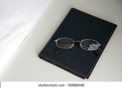 Closeup of eyeglasses and diary on white background, Copy space, Optical instrument for good eyesight.