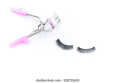 Close-up the Eyelash curler with pink handles and New false Eyelashes style for woman eyes isolated on white background with copy space