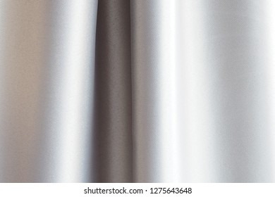 Closeup of fabric strips and roll of curtains in glossy silver tone for soft motion and texture of textile and bright platinum background