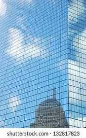 Close-up of the facade of a glass skyscraper reflecting a nearby building