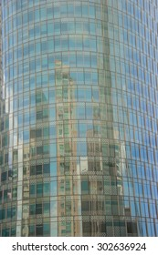 Close-up of facade of office building with sky reflection.