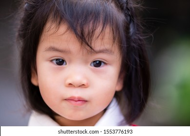 Closeup face of adorable Asian Baby child girl. Kid age 2 years and 9 months. Sweet smile. The face of a happy cute girl. Black hair young woman.