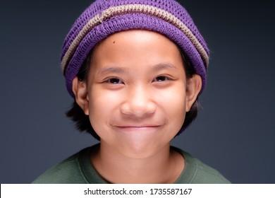 Visage de clôture d'une adorable fille portant un chapeau de laine souriant et regardant la caméra