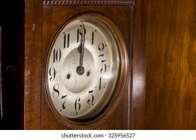 Closeup to the face of an antique pendulum clock made of wood, glass and bronze