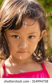 Closeup Face of Asian Little Girl with Sunblock Cream Before Swimming