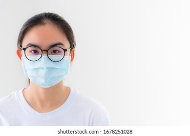 Closeup face Asian young woman wears glasses and mask to protect against Coronavirus looking at camera, Thailand girl people on white background blank or copy space for anti virus Covid 19 concept