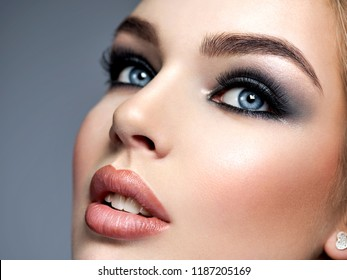 Closeup face of a beautiful girl with  makeup in style smoky eyes. Sexy and gorgeous blonde woman with blue eyes. Portrait of an attractive female posing at studio.