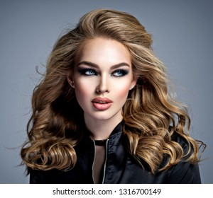 Closeup face of a beautiful girl with  makeup in style smoky eyes. Sexy and gorgeous blonde woman with long curly hair. Portrait of an attractive female posing at studio.