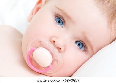 Closeup face of a beautiful newborn girl with blue eyes