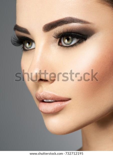 Nahaufnahme des Gesichts einer schönen Frau mit langen Wimpern. Porträt eines hübschen jungen Mädchens. Attraktive sexy Dame, die sich im Studio auf grauem Hintergrund posiert.