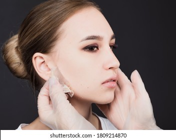 Close-up of the face of a beautiful woman with a face mask on a dark background. The concept of cosmetology, beauty and preservation of youth