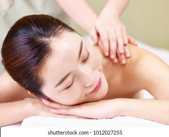 close-up of face of a beautiful young asian woman lying on front on bed receiving massage in spa salon.