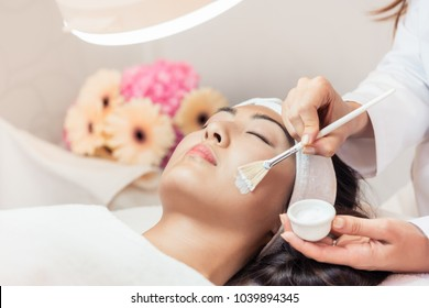 Close-up of the face of a beautiful young Asian woman relaxing during rejuvenating facial massage with brushes in a contemporary beauty center