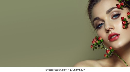 Close-up face of a beautiful young blue-eyed girl with natural make-up. Holds red decorative berries in the face as a decoration.