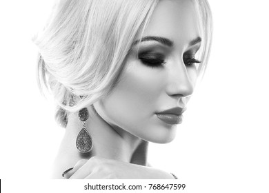 Close-up face of blonde hair model girl with clean skin, salon stage make-up and diamond earrings over white background. Black and white