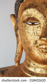 Closeup of the face of buddha's image covering with gold leaf.