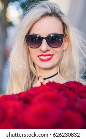 Close-up face of cheerful lady in glasses who keeps red roses, outdoors