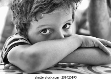 Close-up of the face of a child, with the crossed arms, crying and looking at the camera