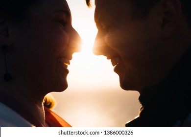 A close-up face of the couple in love who sincerely laugh and between them are sun rays