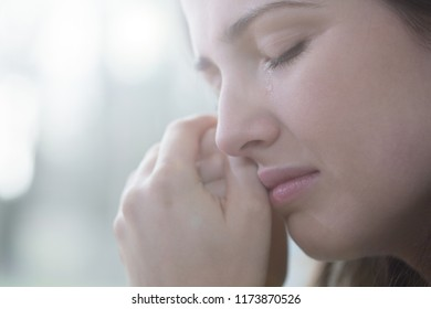 Close-up of face of crying teenager with mental disorder against blurred background