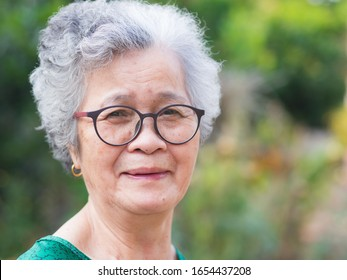 Close-up of face elderly woman smiling happiness, short white hair and looking at the camera, standing in garden. Asian senior woman healthy and have positive thoughts on life make her happy every day