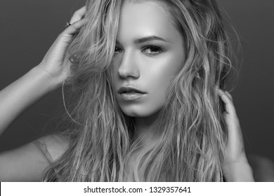 Closeup face fashion beauty portrait of young beautiful caucasian blonde woman with wet hair and makeup posing against gray background.