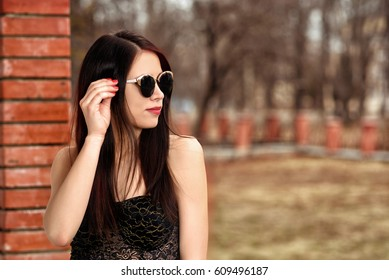 Closeup face fashion portrait of young beautiful pretty stylish girl with long brunette hair and red lips posing in city wearing sunglasses