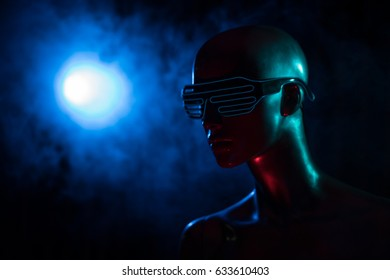 Closeup face of female mannequin in blue led glasses over dark smokey background