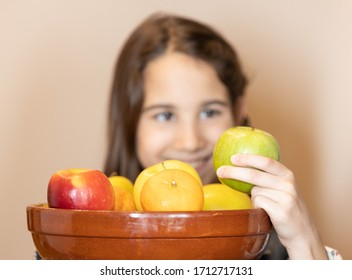 Close-up of the face of a girl choosing fruit behind the fruit bowl