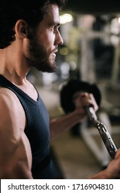 Close-up of face of handsome bearded young man with muscular wiry body wearing sportswear working out with barbell during sport workout training in modern dark gym. Concept of healthy lifestyle.