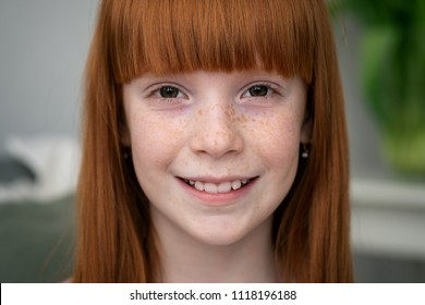 Close-up of face happy little ginger girl with freckles smiling