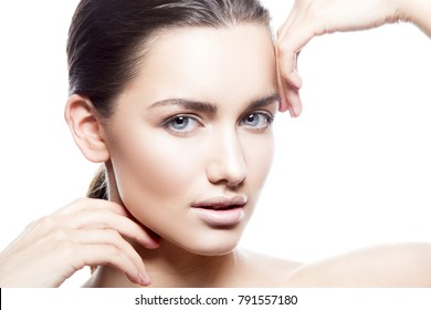 Close-up face of model woman touching her skin. Natural nude make-up, blue eyes, brunette hear. Skincare treatment woman apply cream health concept. Isolated on white background