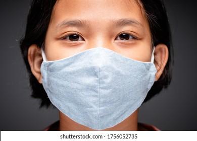 Gros plan sur le visage d'un enfant de neuf ans portant un masque bleu en tissu et regardant la caméra, un enfant asiatique évite une pandémie de vif-19